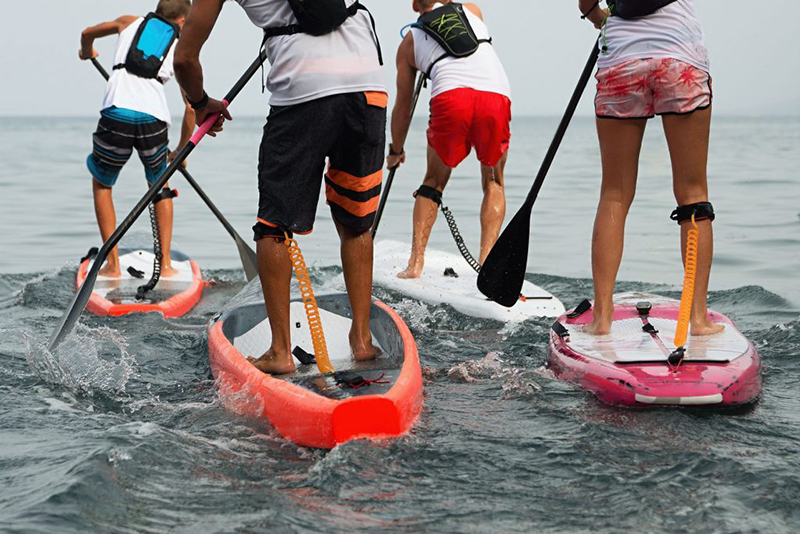 Group of people on stand up paddle board SUP