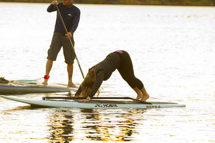 woman doing yoga pose on stand up paddle board