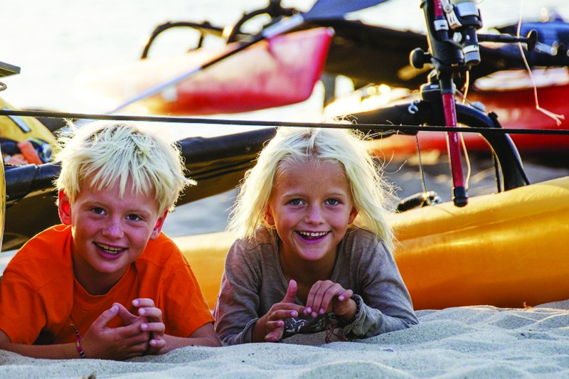 two children laying on sand in front of kayak